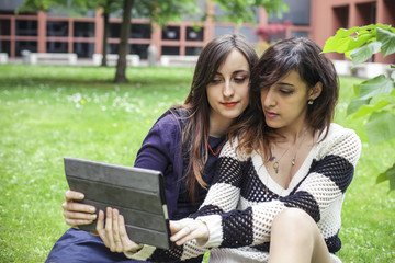 Two girls taking a selfie with a tablet pc
