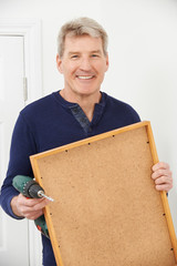 Mature Man Drilling Wall To Hang Picture Frame