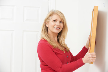 Mature Woman Hanging Picture On Wall