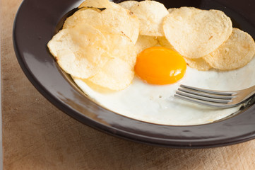 view of a fried egg served on dark dish with fries
