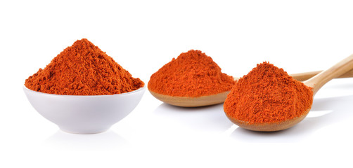 Powdered dried red pepper in a white bowl and wood spoon on whit