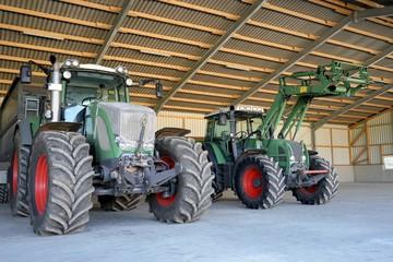 Fototapete - Lanwirtschaftliche Maschinenhalle mit zwei großen Traktoren