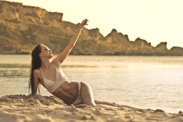 Classy woman wearing a white swimsuit sitting on the sand