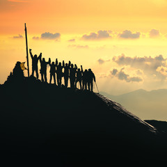 Teamwork. A group of people are standing on the top of the mountain.