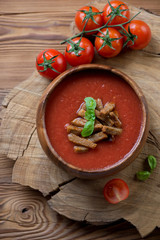Tomato soup gazpacho over wooden background, view from above