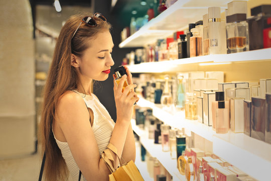 Classy woman choosing a perfume inside a perfumery