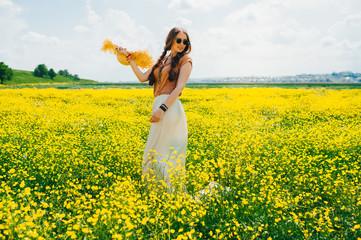 Romantic hippie girl standing in a field. Summer. Hippie style.