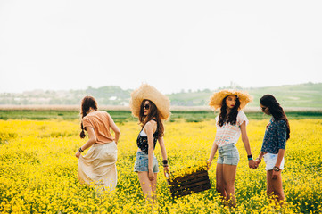 four beautiful hippie girl in a field of yellow flowers