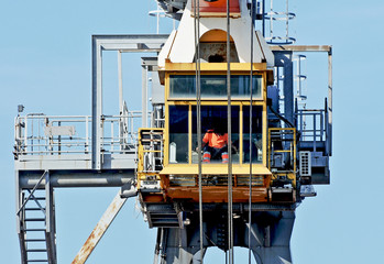 Dockside crane with worker pilot in the cabin.
