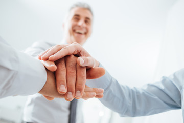 Cheerful business people stacking hands