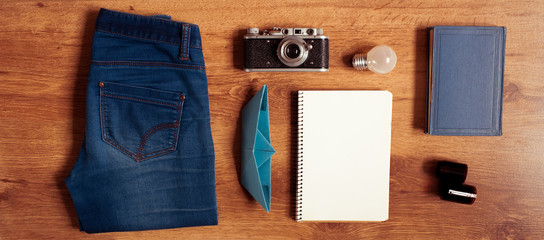 Vintage hipster packing: clothes, old camera, notebook,book,origami boat on wooden floor. Top view.