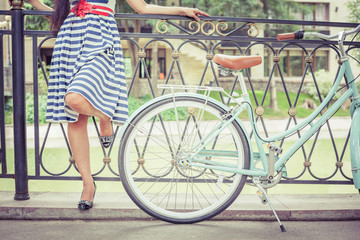 Young girl dressed in a striped dress standing near fence, near vintage city bike at the park. Freedom woman with her happy vacation travel at European city, Paris