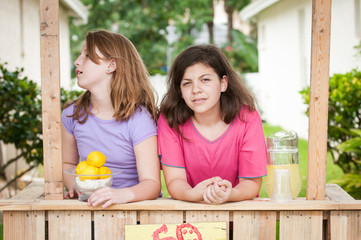 Two boted young girls selling lemonade