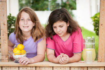 Two bored young girls selling lemonade