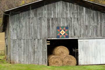 Wooden barn filled with hay, decorated with quilt block.