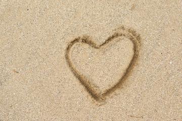 Heart shape drawing on a sand beach