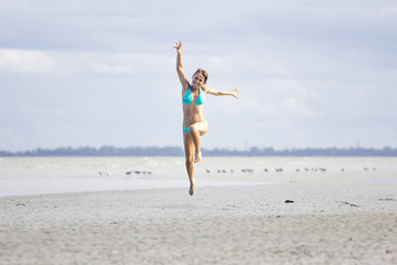 Woman running and jumping high for life on beach