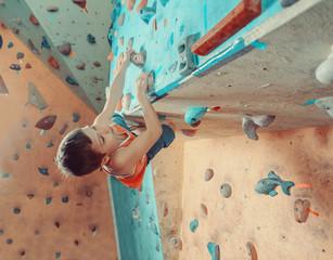 Boy climbing in gym