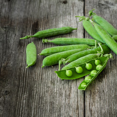 fresh green peas over a rustic wood table