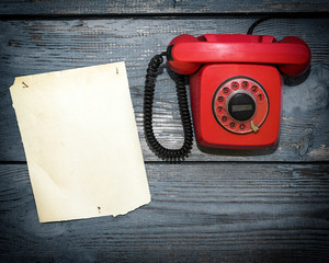 Vintage red phone and a piece of paper to write