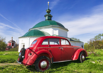 Red classic car against the backdrop of an old church in Suzdal