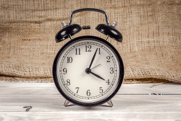 Classic alarm clock on a wooden table
