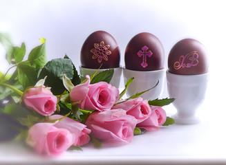 Пасхальный натюрморт с крашенными яйцами в подставках и розами на столе.