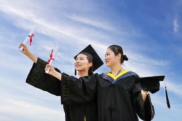 Beautiful female graduates wearing graduation gown