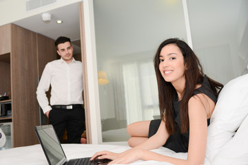attractive young brunette business woman with man working computer in hotel room