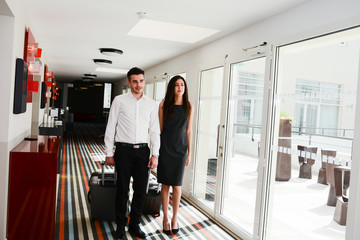 two young business person man and woman walking in a public space corridor