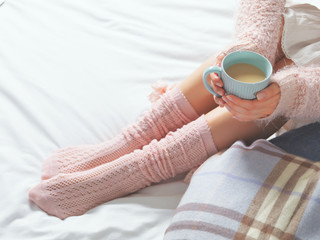 Woman relaxing at cozy home atmosphere on the bed with cup of coffee or cocoa.