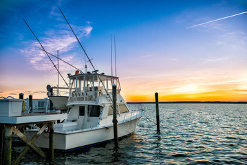 fishing boat on the pier at sunset on the lake