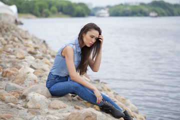 Young beautiful brunette girl sitting on the rocks on the river