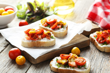 Tasty fresh bruschetta with tomatoes on cutting board on grey wo