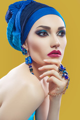 Beautiful middle eastern woman with hijab with blue scarf and blue jewelry and red lips on yellow background, studio shot. looking at camera. side looking.