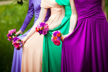 Bridesmaids in colorful dresses with bouquets of flowers