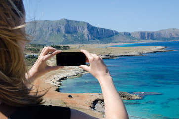 Girl takes picture with smartphone on a bay with panoramic seaviews in Sicily Italy