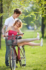 Young couple having fun on the bicycle