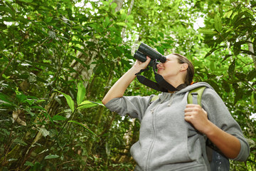 hiker watching through binoculars wild birds in the jungle