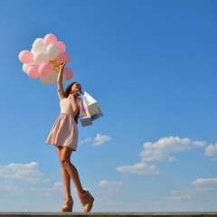 Beautiful girl holding shopping bags and colored ballons over bl
