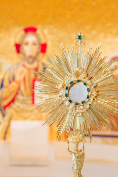 Eucharistic adoration monstrance on the altar with the image of Jesus Christ in the background