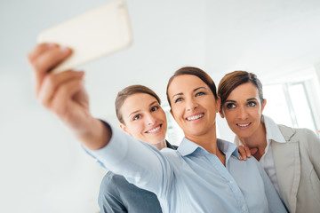 Smiling business women team taking a selfie