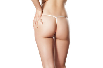 pretty female buttocks in a thong on a white background