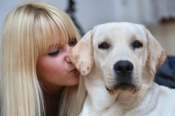 Blonde girl enjoying with his yellow Labrador in apartment