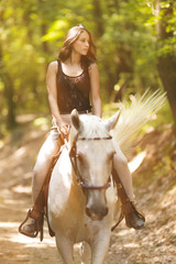 Outdoor photo from a beautiful young women with her horse