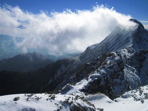 赤岳と雲間から富士山