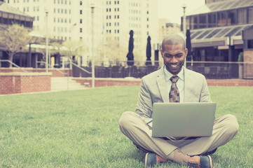Handsome happy businessman working with laptop outdoors