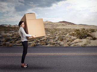 Young woman carrying heavy large box package