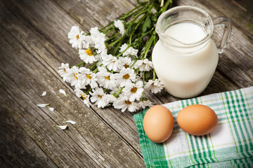 Milk and flowers on a wooden background
