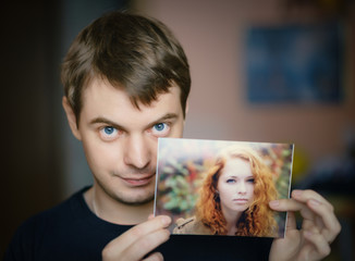 Young man holding in hand photo of a beautiful girl.
